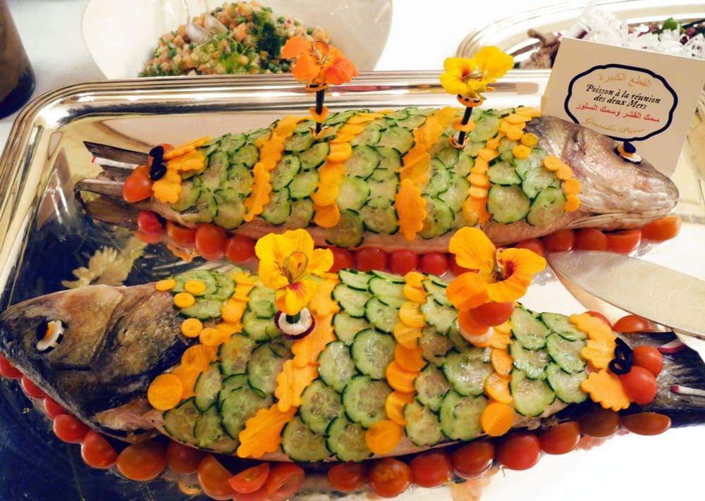 Poisson cuit décoré avec des concombre, des carottes et des fleurs comestibles.
